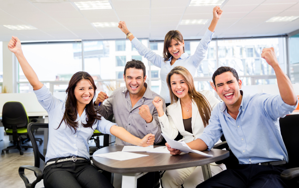 Successful business team with arms up at the office